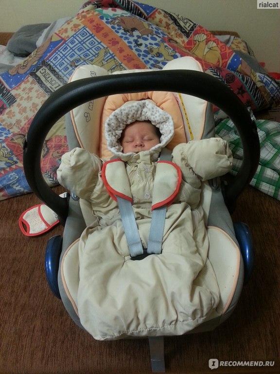 Новорожденный в коляске в комбинезоне